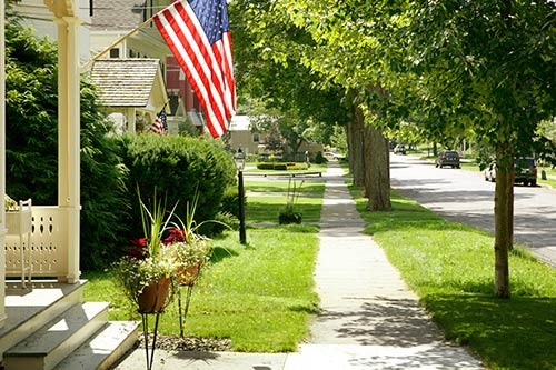 Small Town - American Flag Hanging From Front Porch